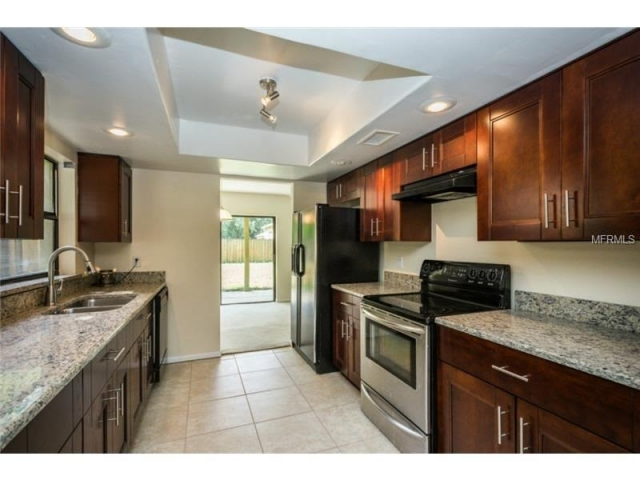 Kitchen remodel with all wood cabinets and granite countertops.