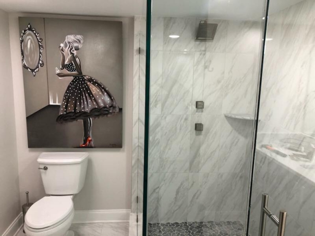 Outdated tile taken out.  Jacuzzi tub totally taken and replaced with a glass shower with Carrara Marble on the walls and mosaic tiles on the floor.  All wood floating vanity with carrara marble top installed.