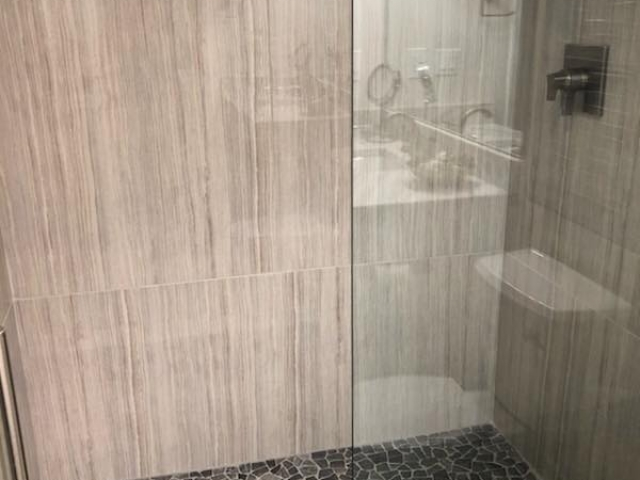 Outdated tile taken out.  New glass shower with Carrara Marble on the walls and mosaic tiles on the floor.  All wood floating vanity with carrara marble top installed.